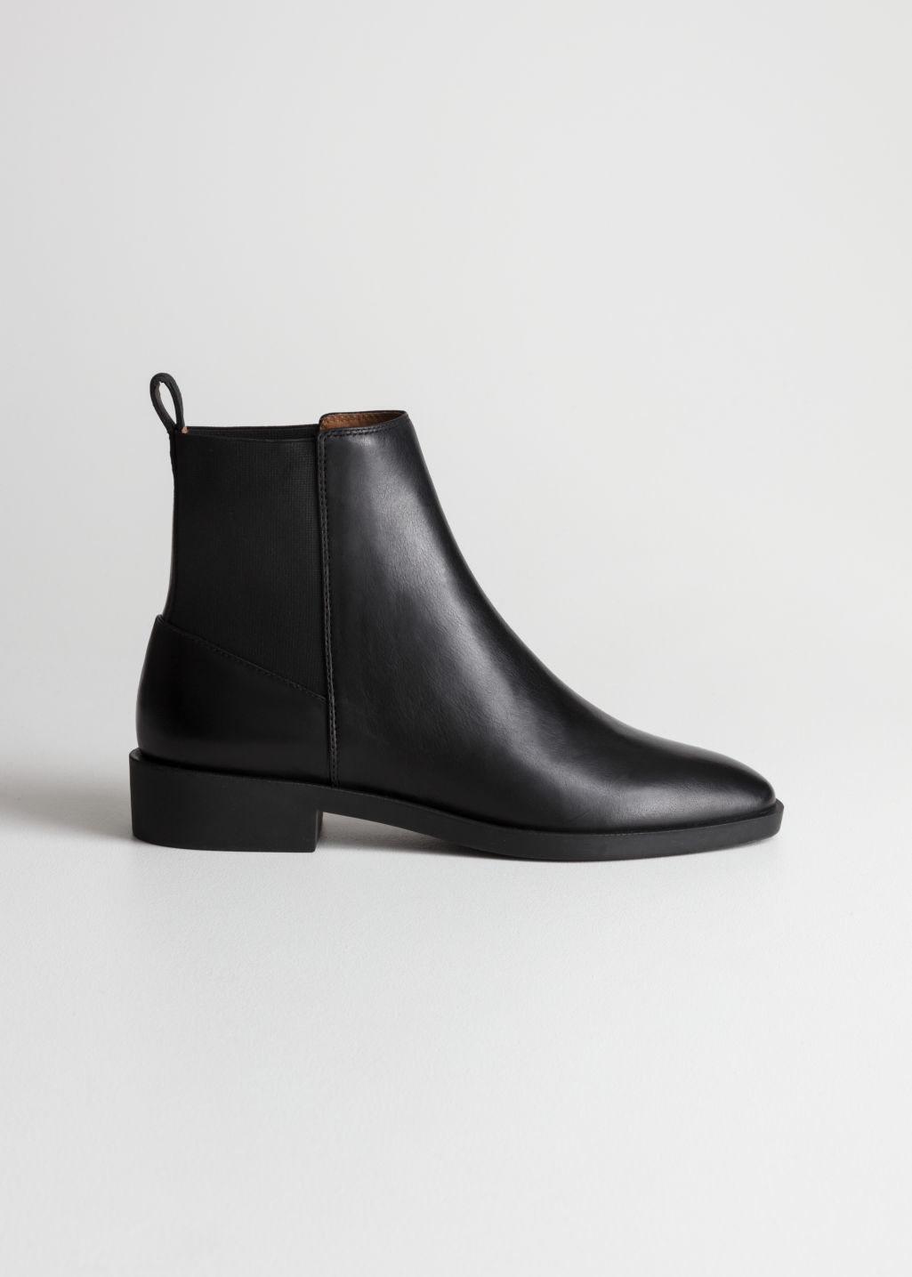 Front image of Stories chelsea leather boots in black