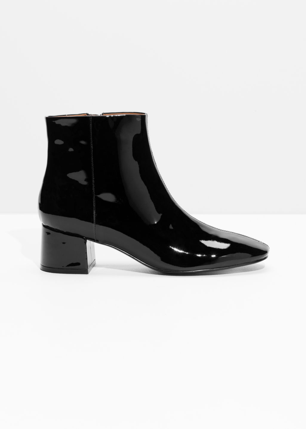 Front image of Stories patent leather ankle boots in black