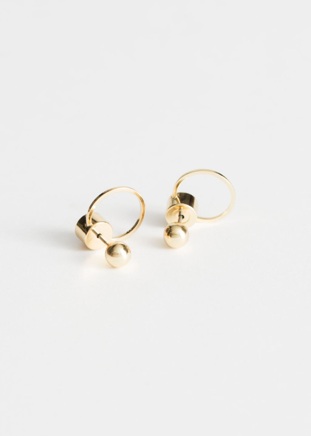 Front image of Stories circular drop-back earrings in gold