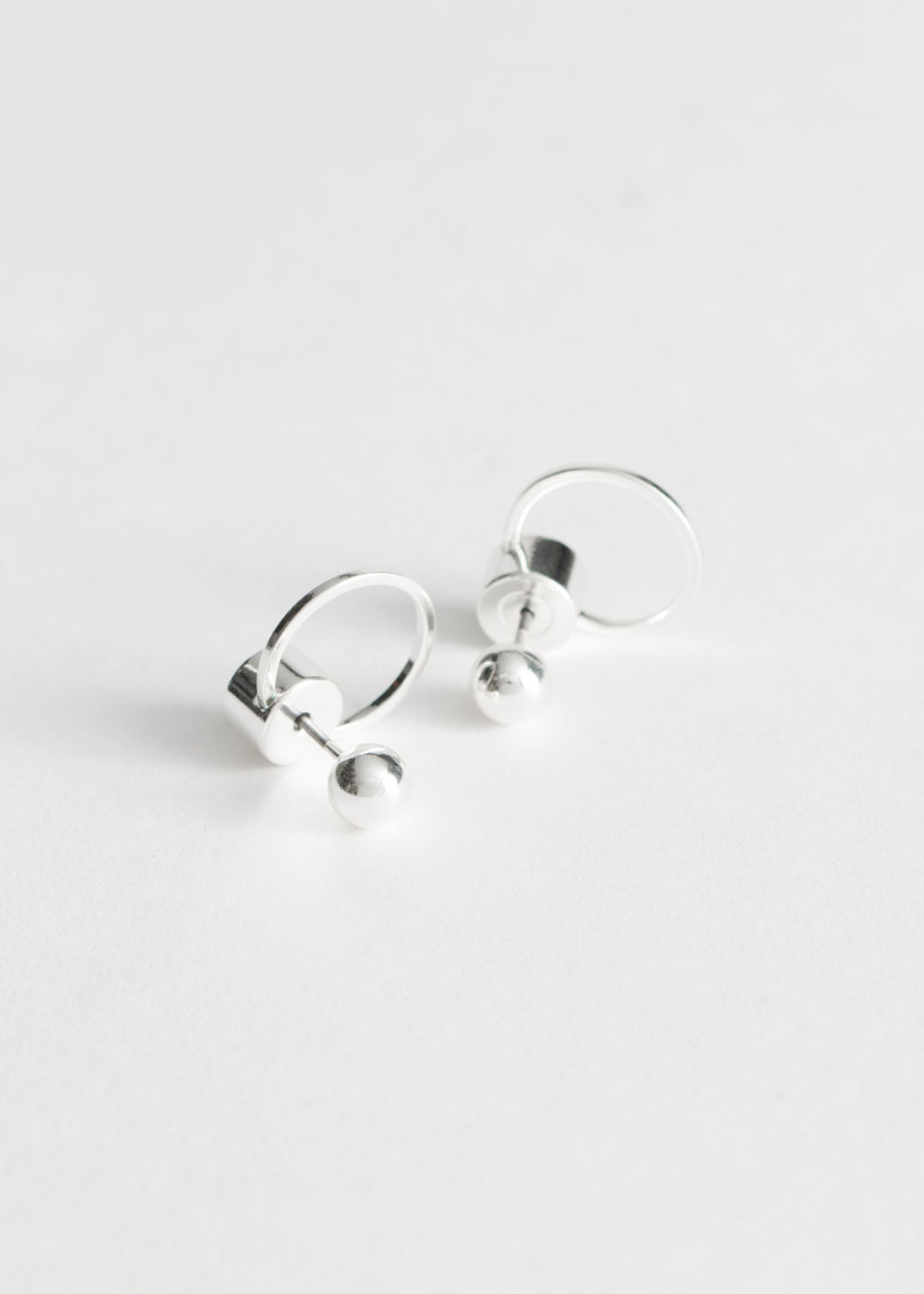 Front image of Stories circular drop-back earrings in silver