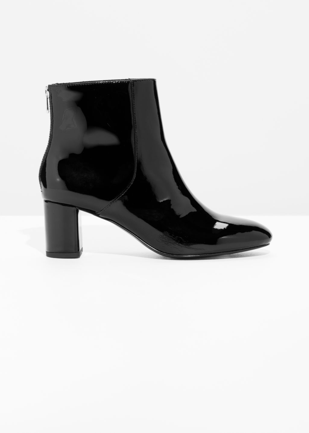 Front image of Stories patent leather zip boots in black