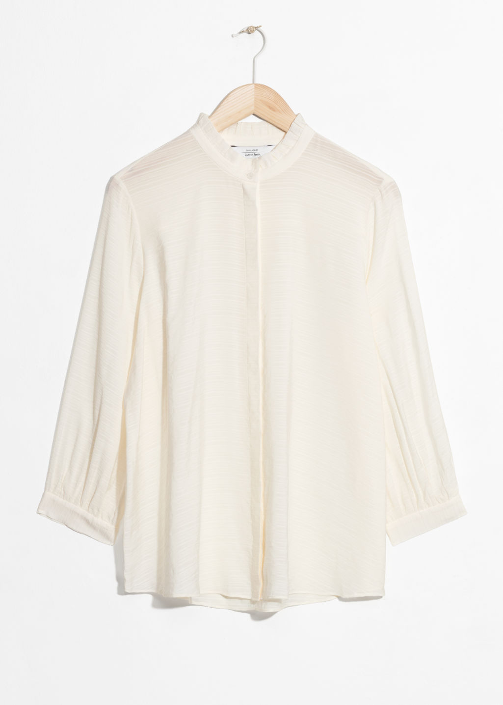 Front image of Stories relaxed ruffle collar blouse in white