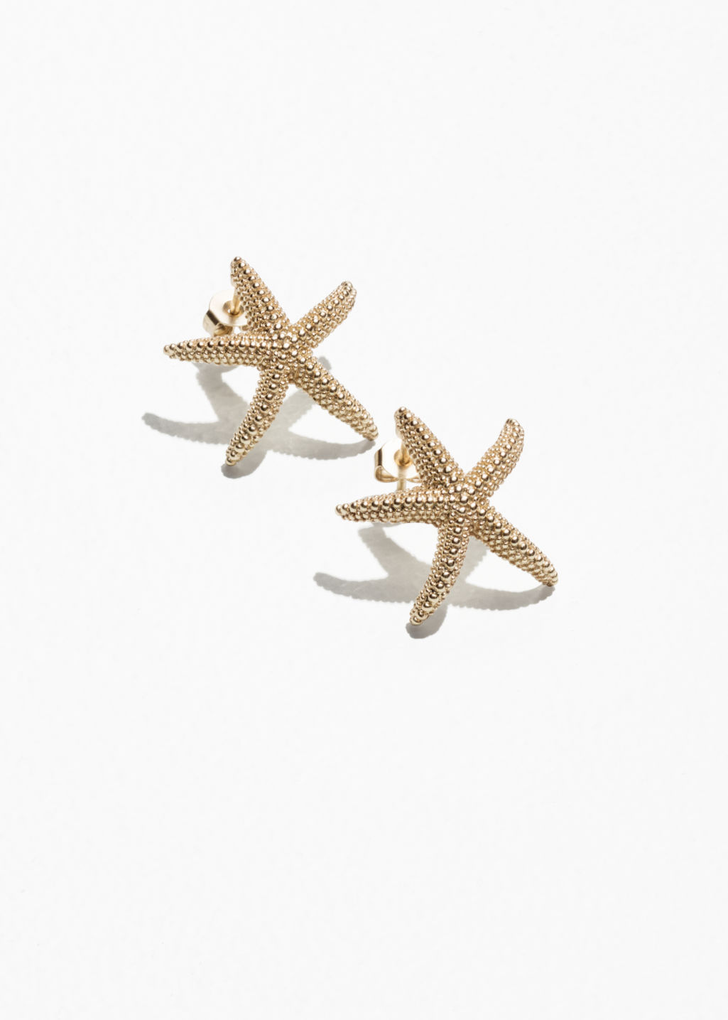 Front image of Stories star fish stud earrings in gold