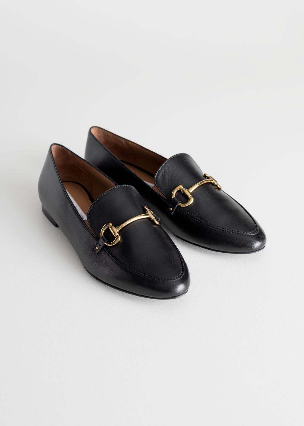 Front image of Stories equestrian buckle loafers in black