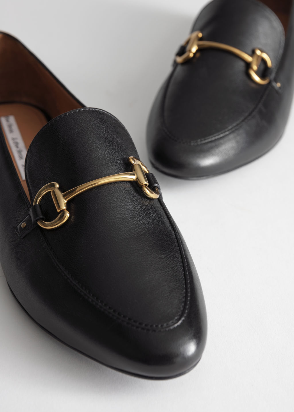 Back image of Stories equestrian buckle loafers in black
