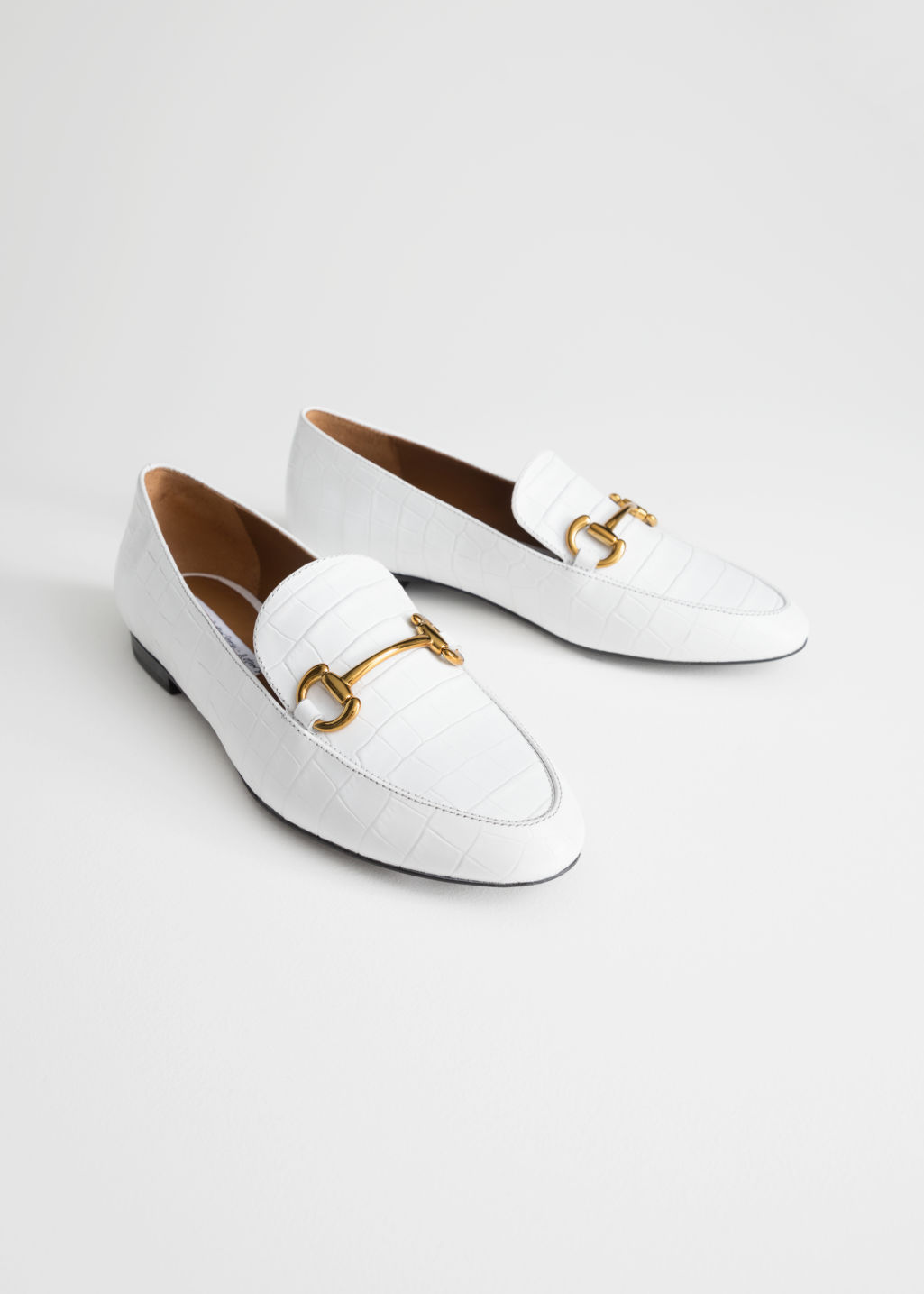 Back image of Stories equestrian buckle loafers in white