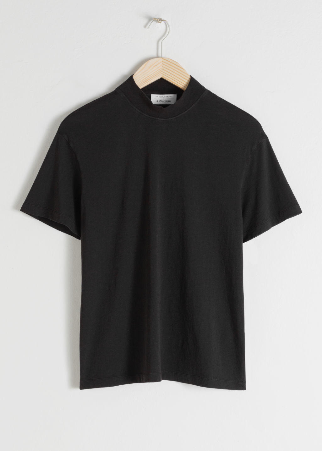 Front image of Stories mock neck tee in black