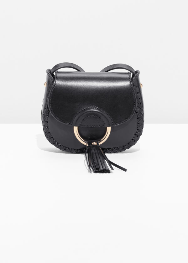 Front image of Stories ring & tassel leather mini-saddle bag in black