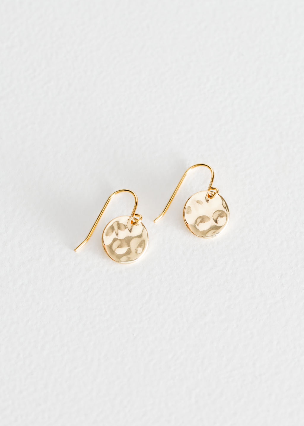 Front image of Stories hammered disc earrings in gold