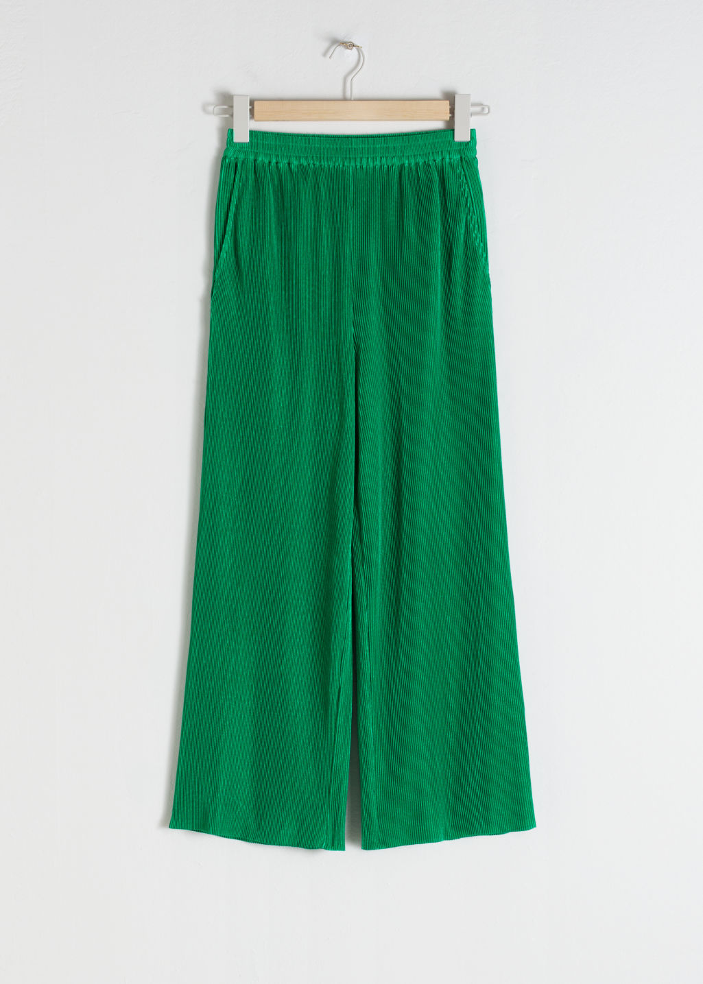 Front image of Stories pleated metallic trousers in green