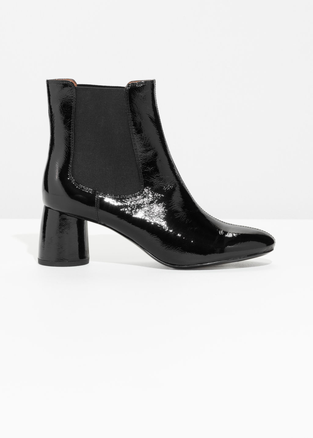 Front image of Stories patent leather boots in black