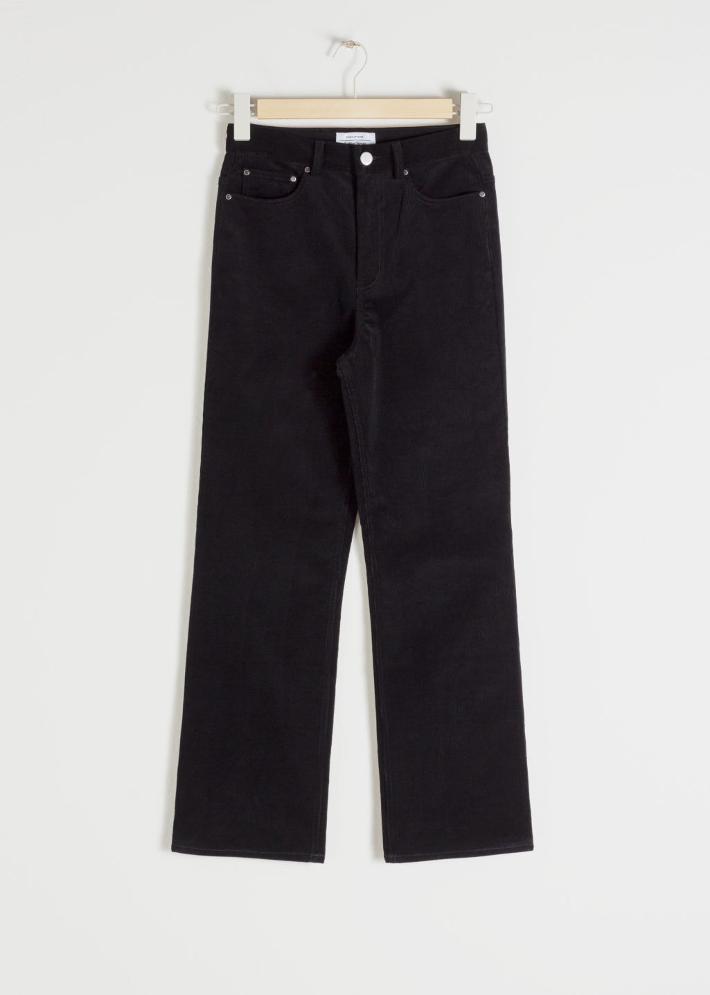 Front image of Stories kick flare corduroy trousers in black