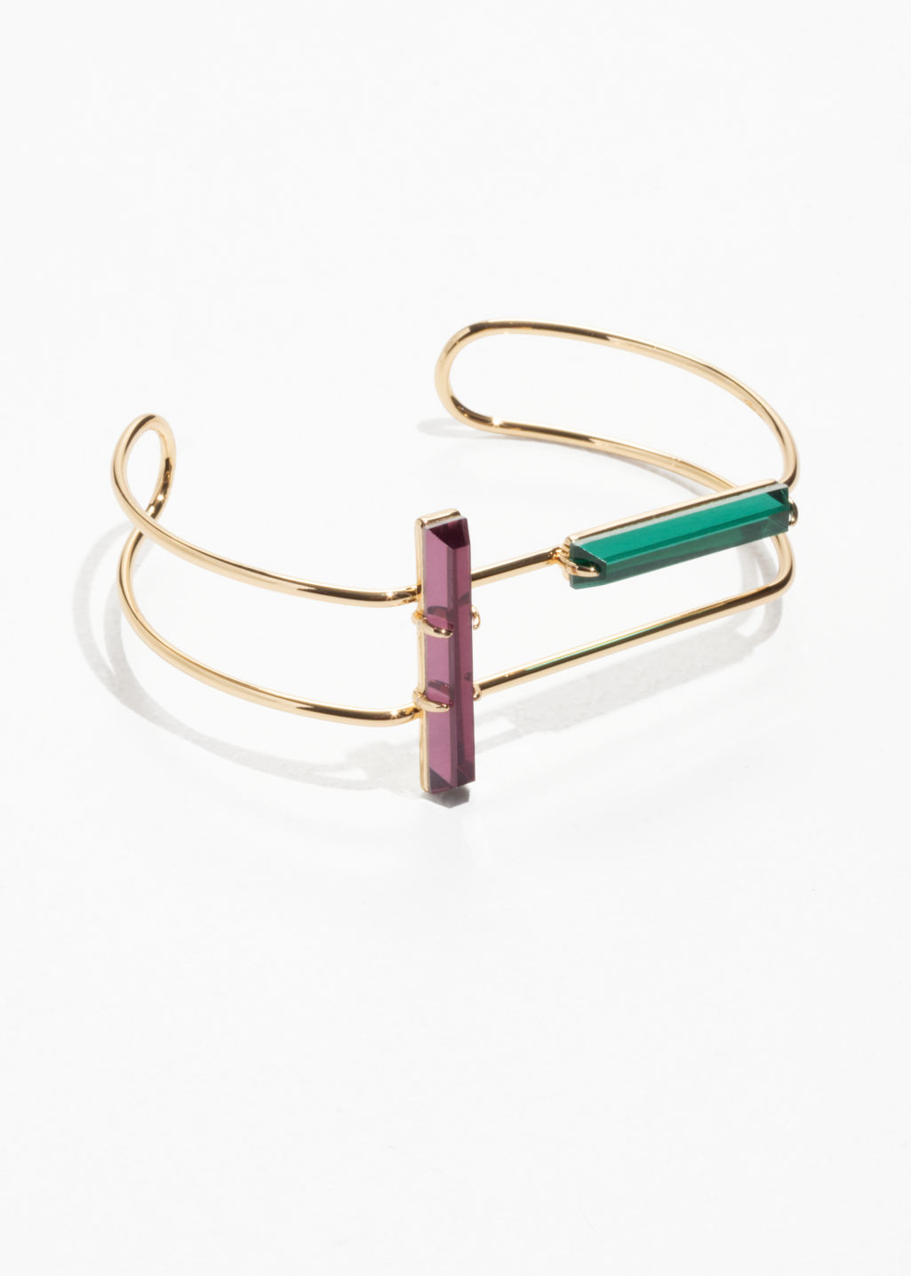 Front image of Stories tubular wire cuff with gems in green
