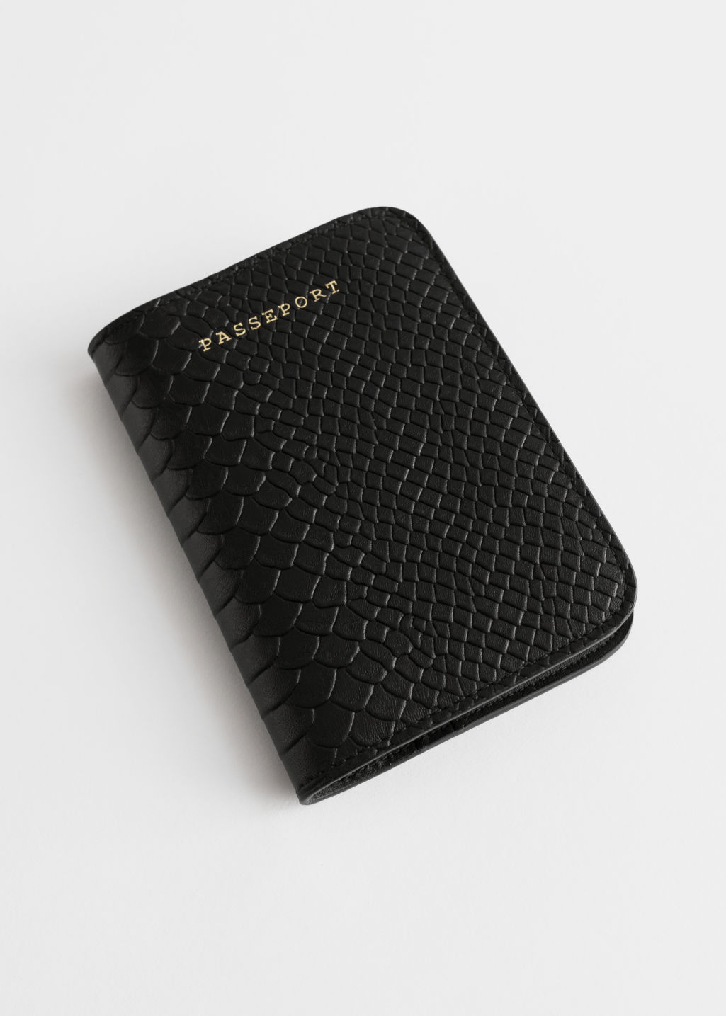 Front image of Stories leather passport holder in black