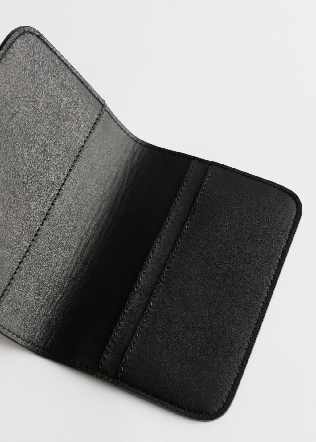 Back image of Stories leather passport holder in black