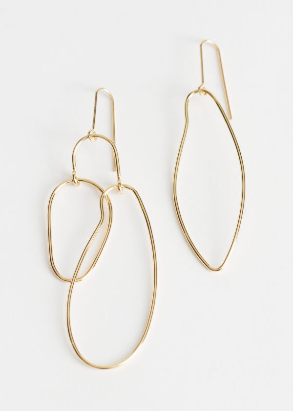 Front image of Stories asymmetrical earrings in gold