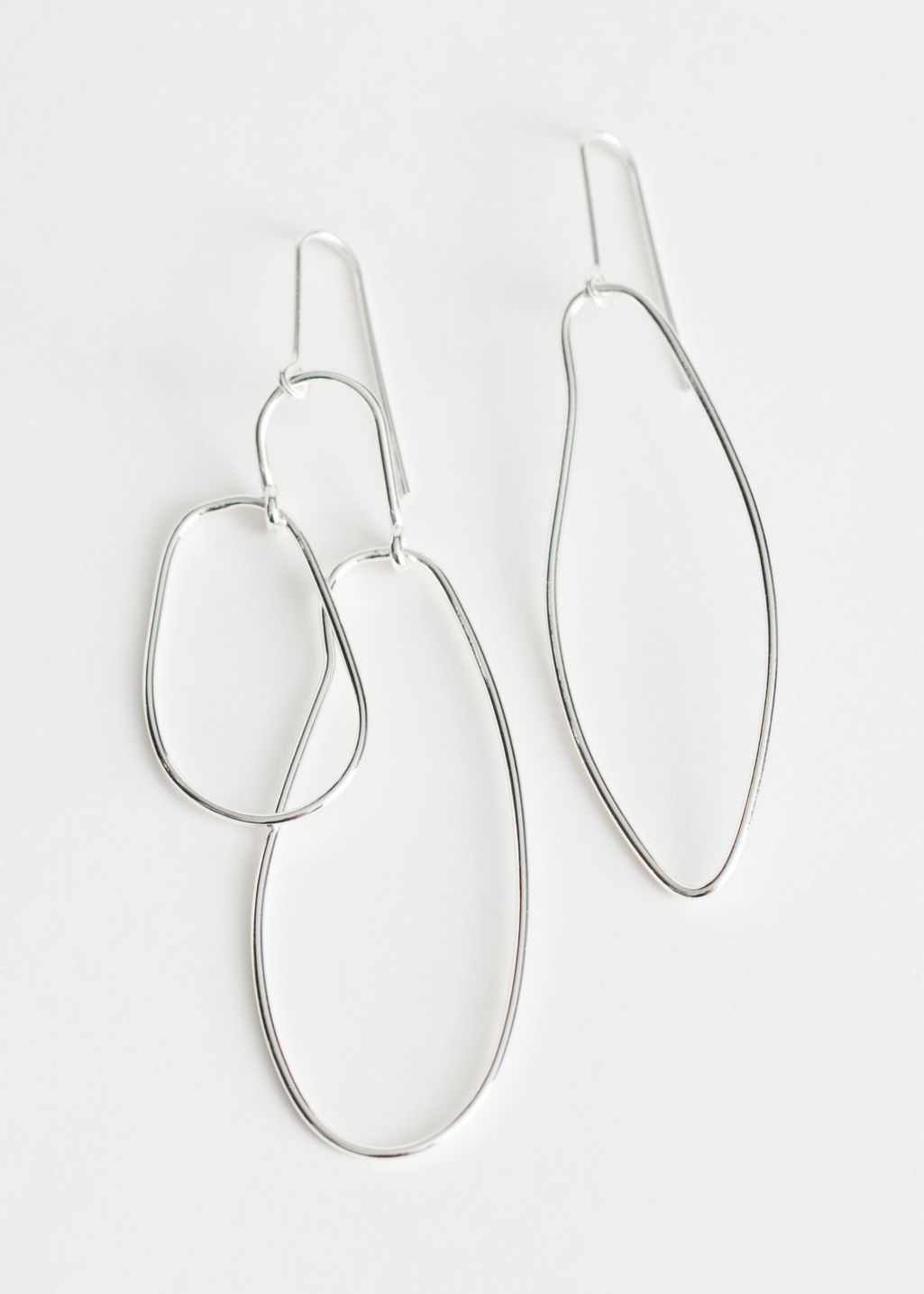 Front image of Stories asymmetrical earrings in silver