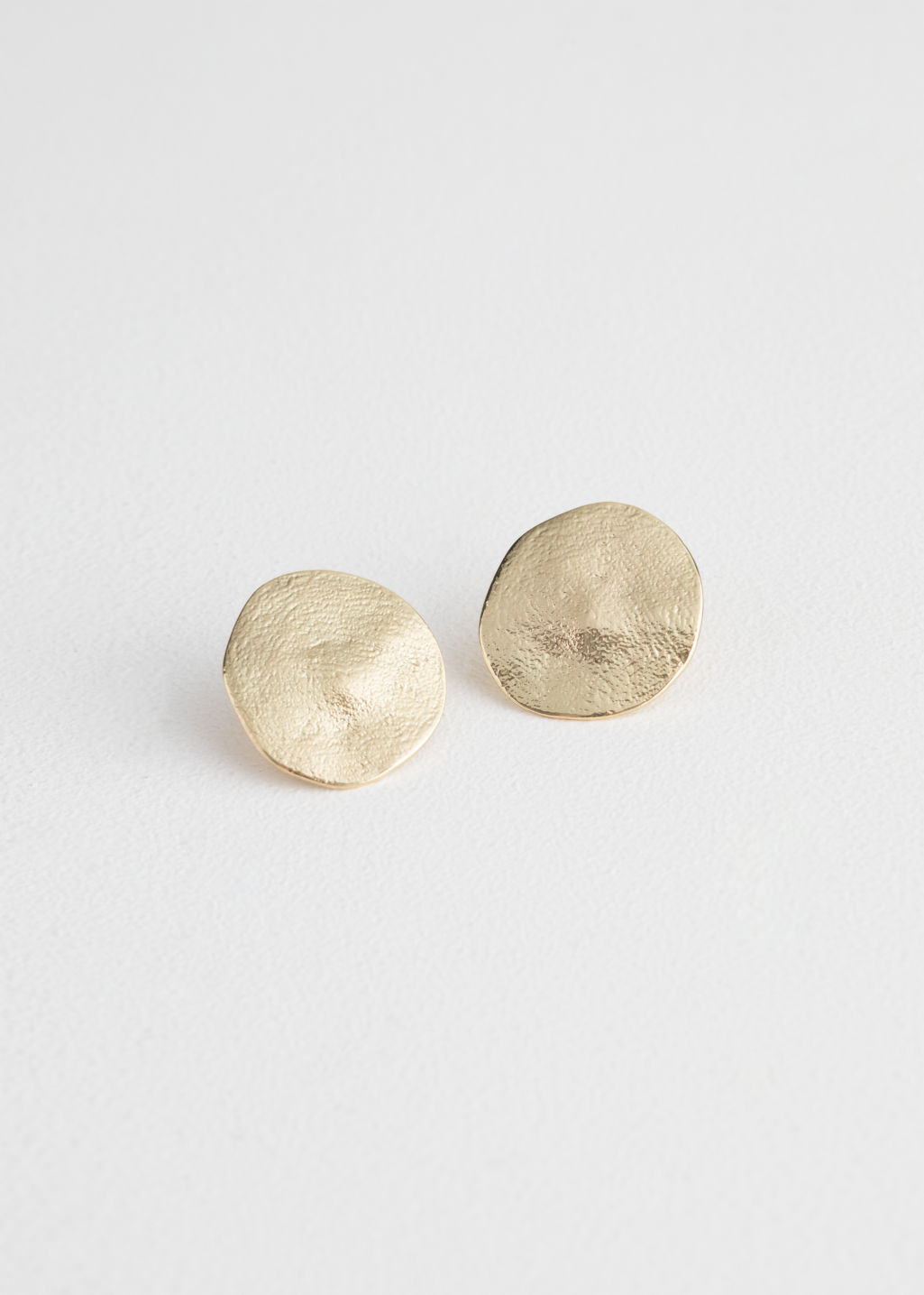 Front image of Stories textured brass earrings in gold