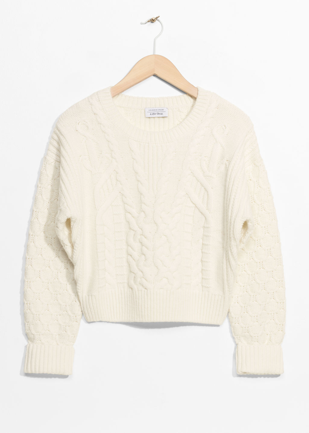 Front image of Stories cable knit sweater in white