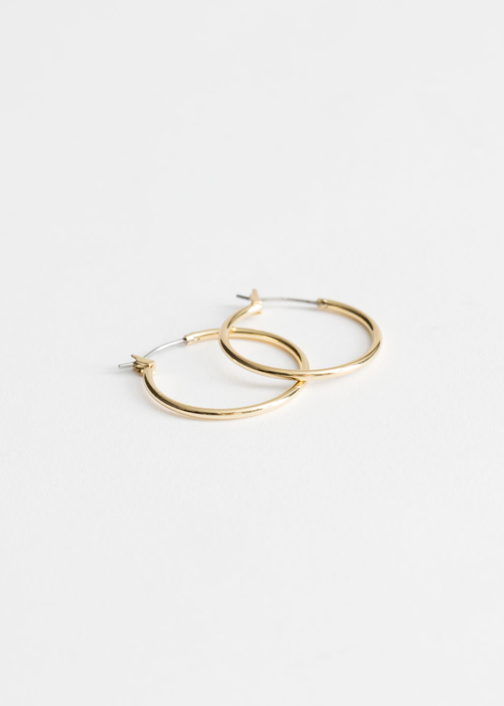 Front image of Stories glossy hoop earrings in gold