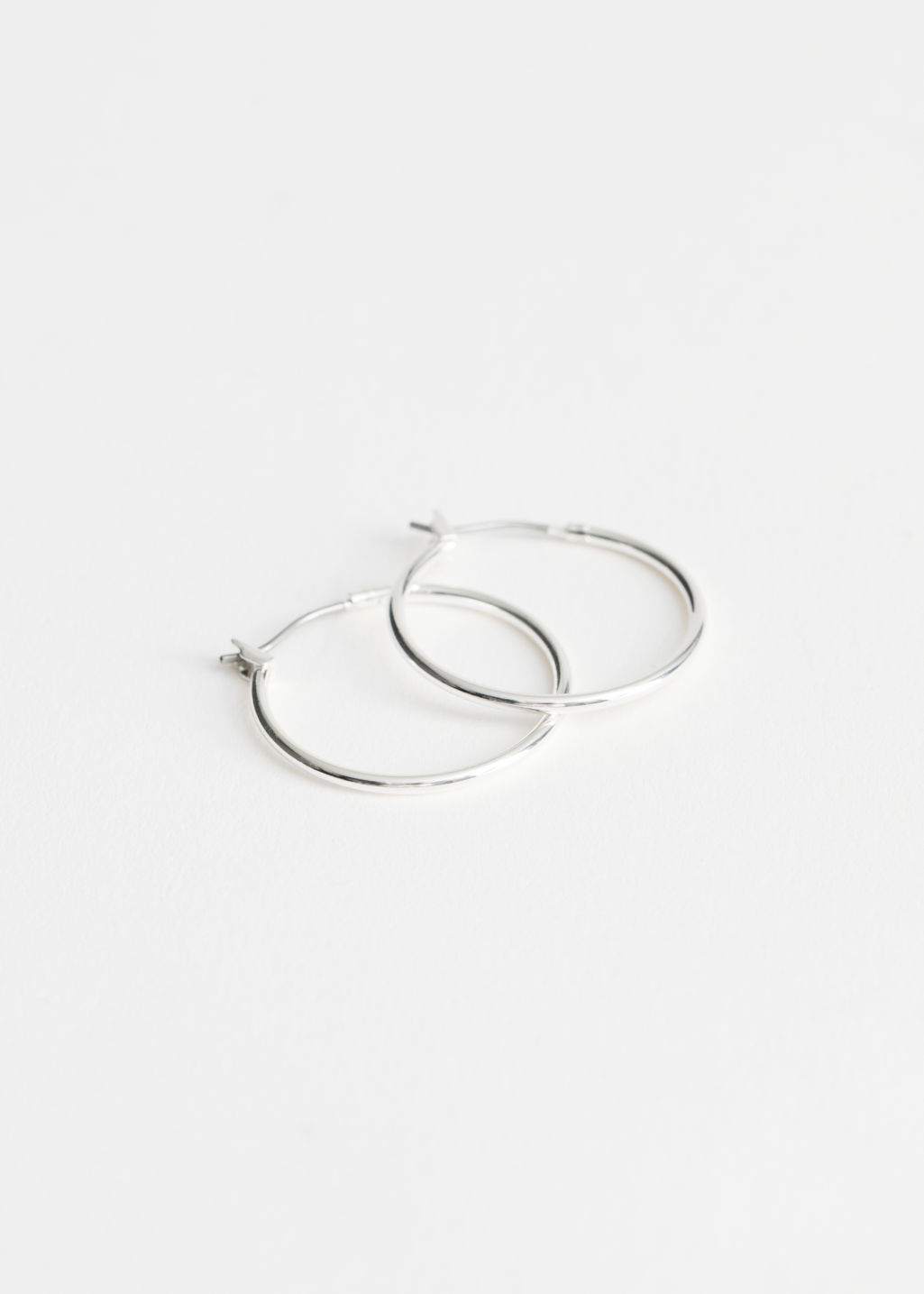 Front image of Stories glossy hoop earrings in silver
