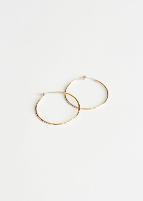Front image of Stories mid size hoop earrings in gold
