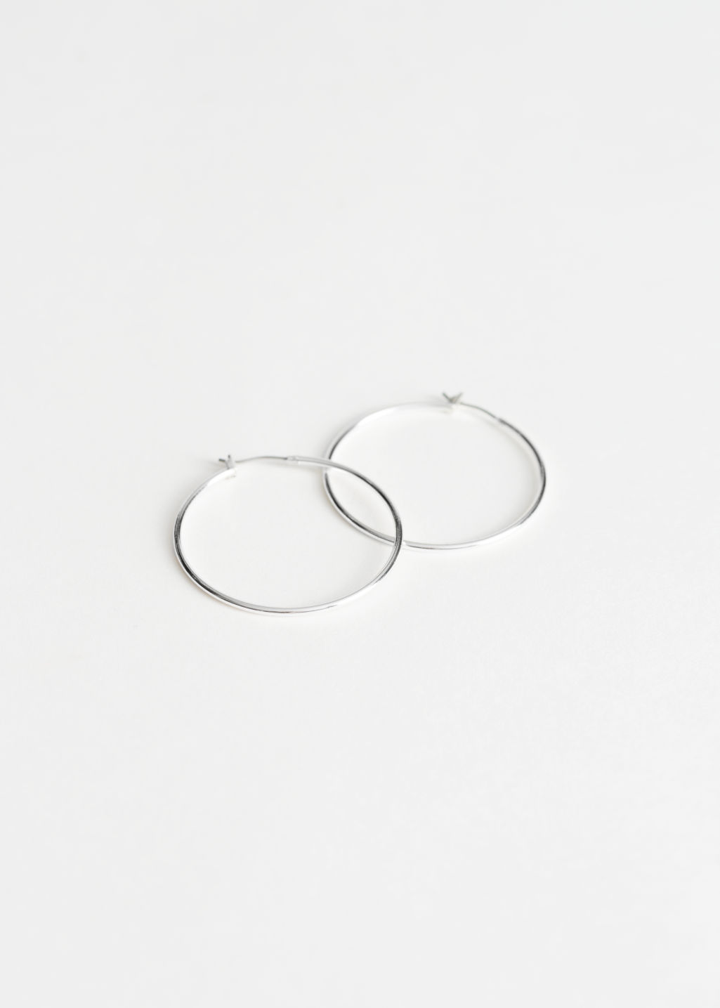 Front image of Stories mid size hoop earrings in silver