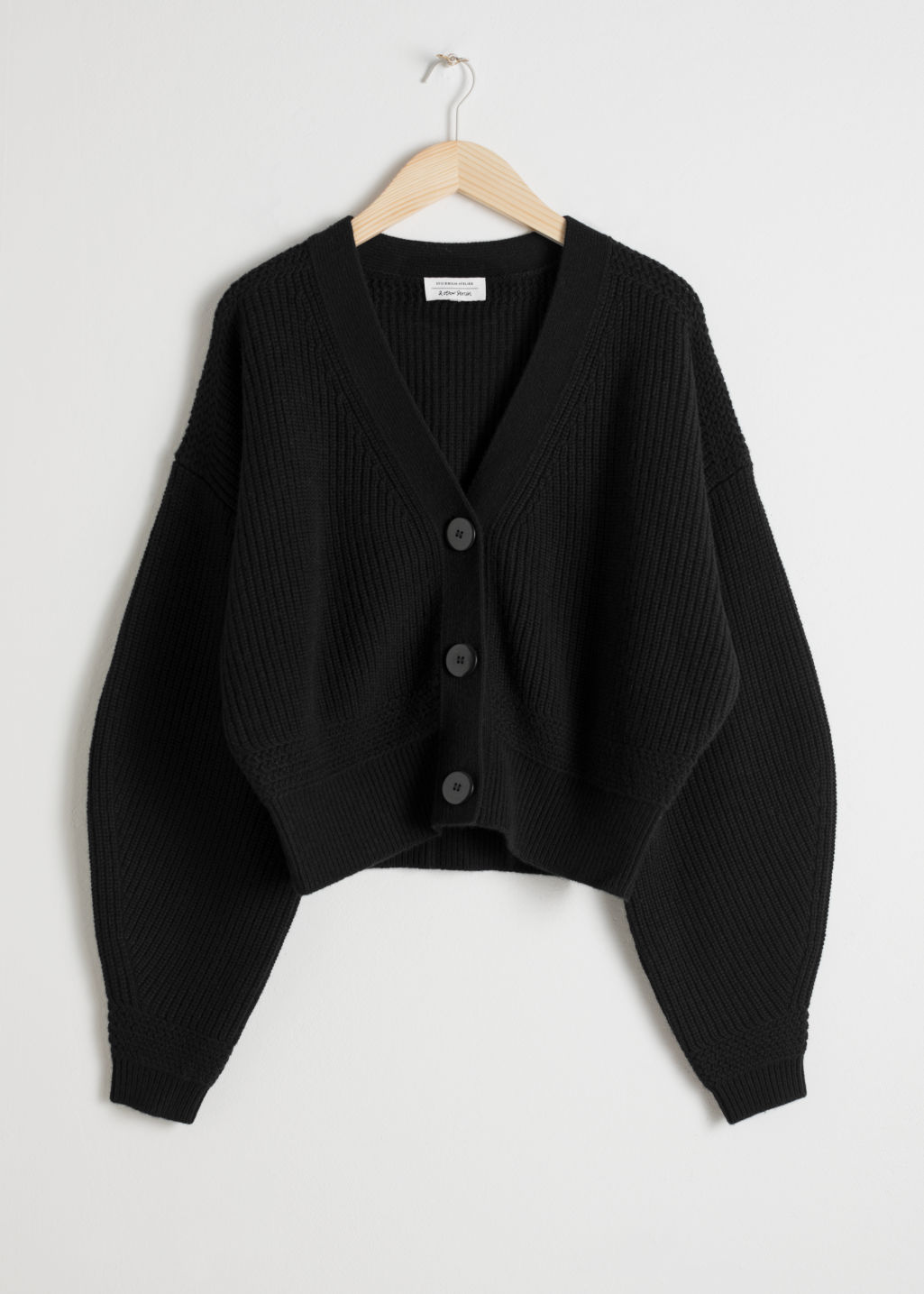Front image of Stories wool button sweater in black