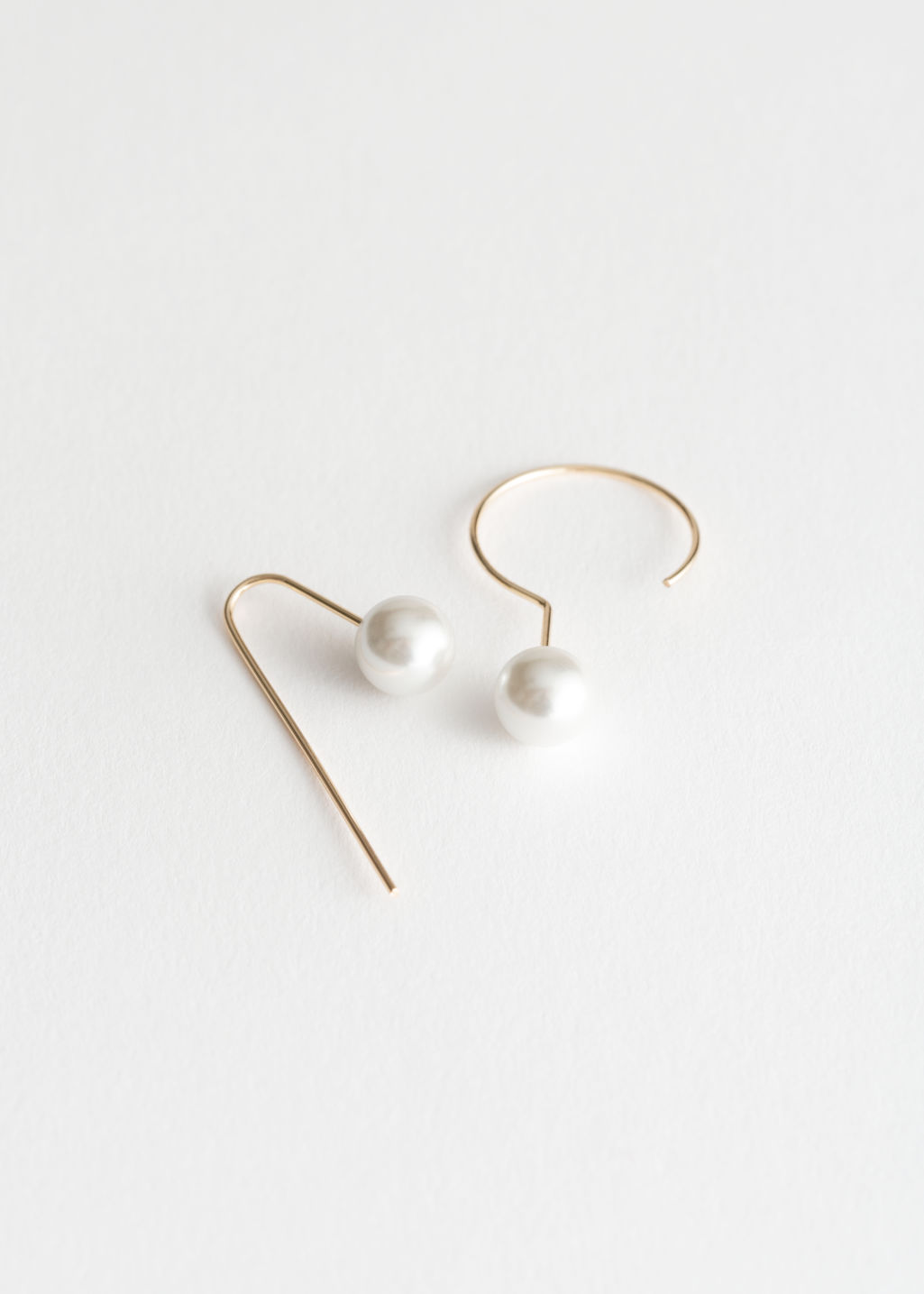 Front image of Stories asymmetric pearl earrings in gold