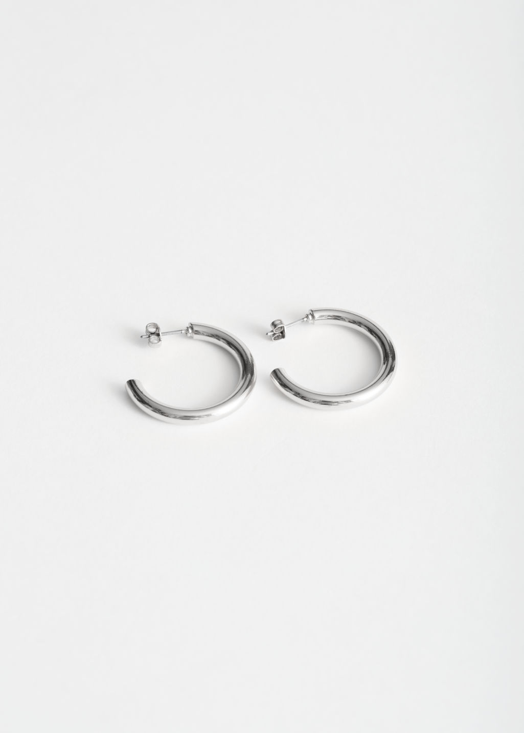 Front image of Stories rose gold hoops in silver