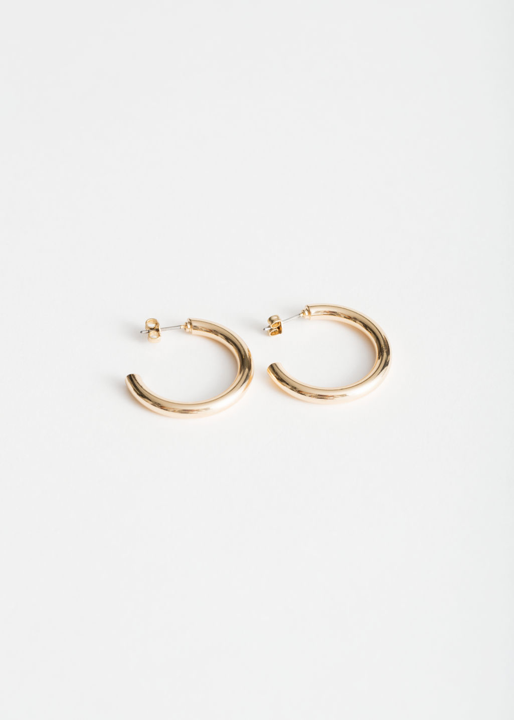 Front image of Stories rose gold hoops in gold