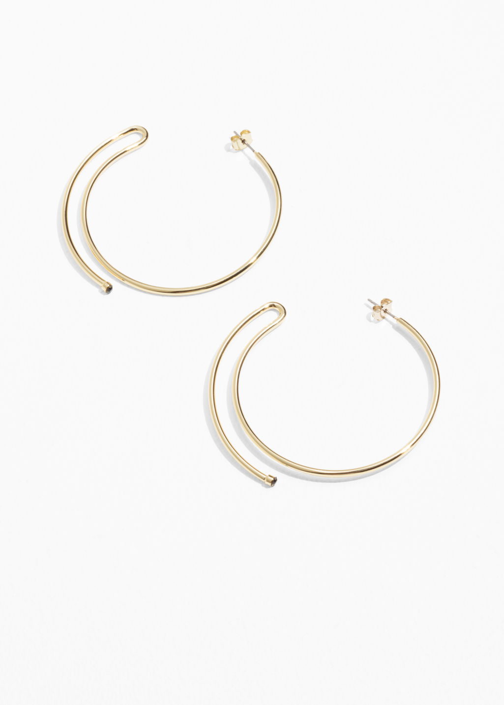 Front image of Stories wire movement hoop earrings in gold