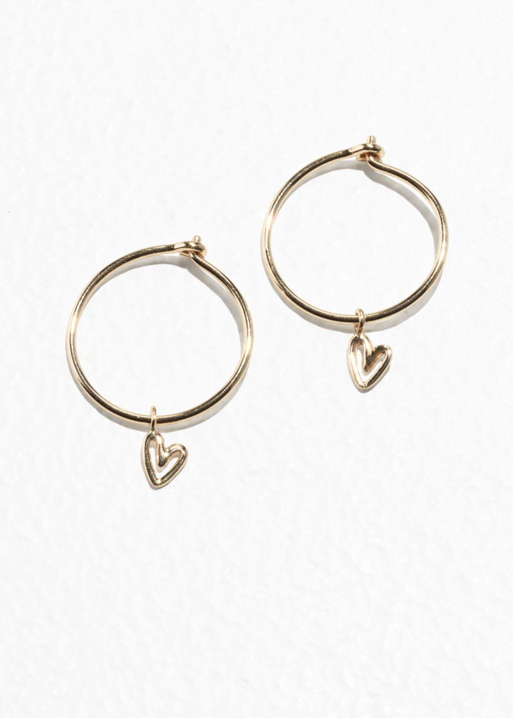 Front image of Stories mini hoops with heart pendant in gold