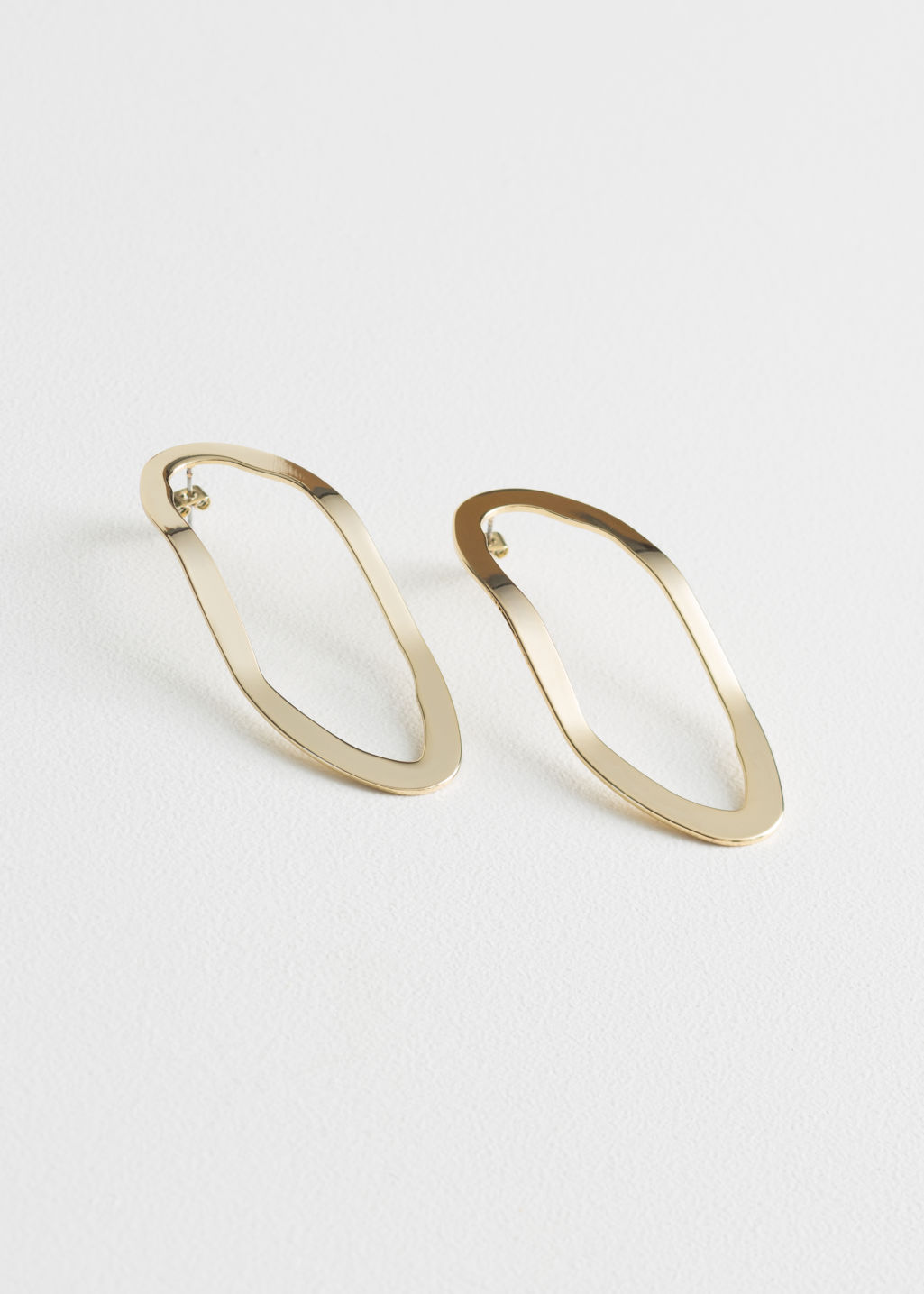 Front image of Stories curved oval earrings in gold