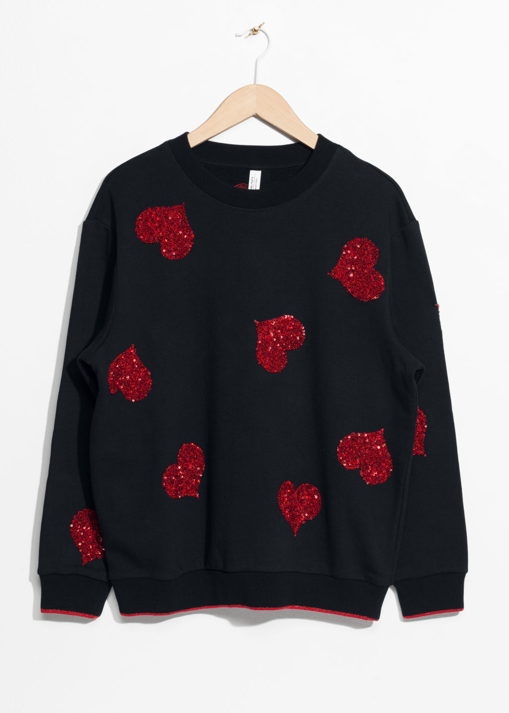 Front image of Stories sequin heart sweater in black