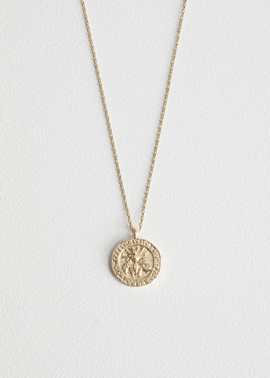 Front image of Stories bee embossed pendant necklace in gold