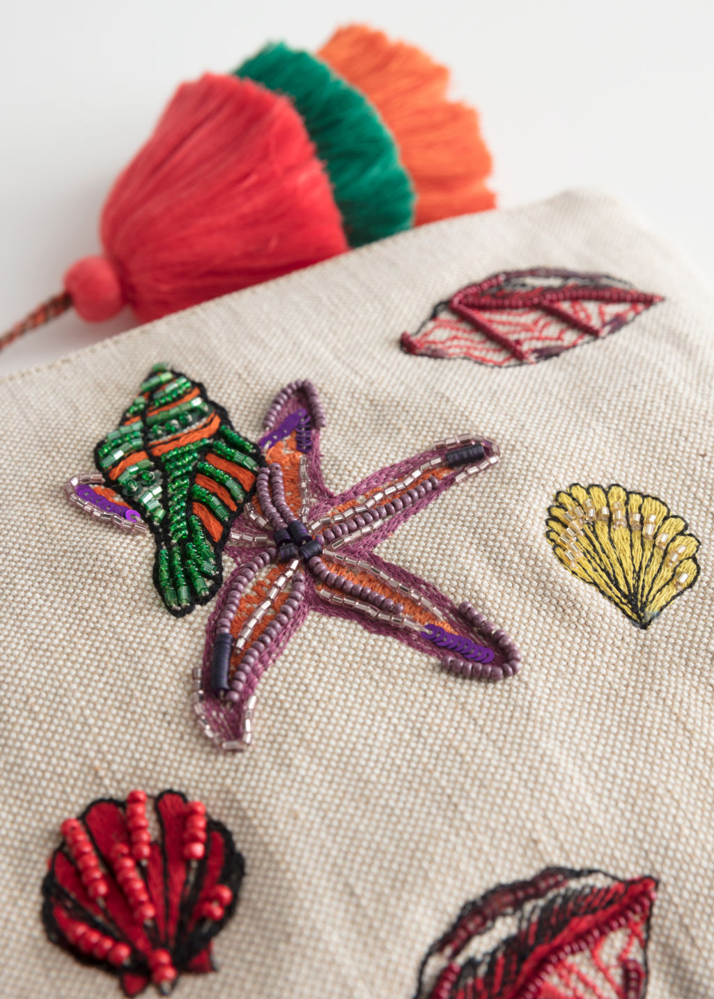 Back image of Stories woven embroidered seashell clutch in beige