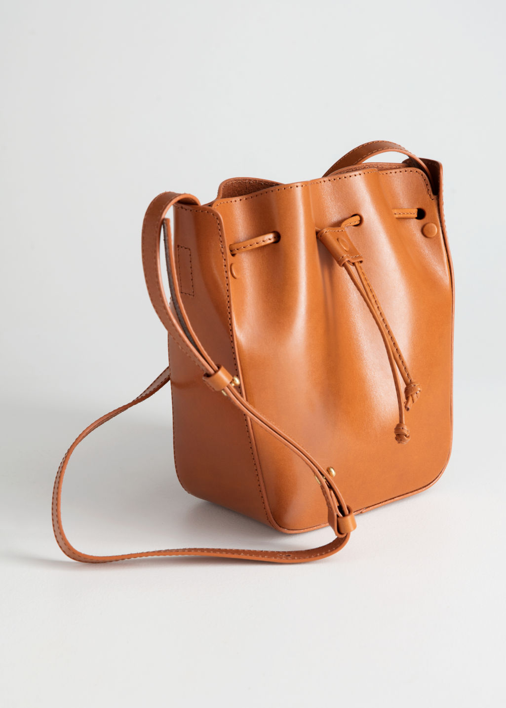 Front image of Stories drawstring leather bucket bag in beige