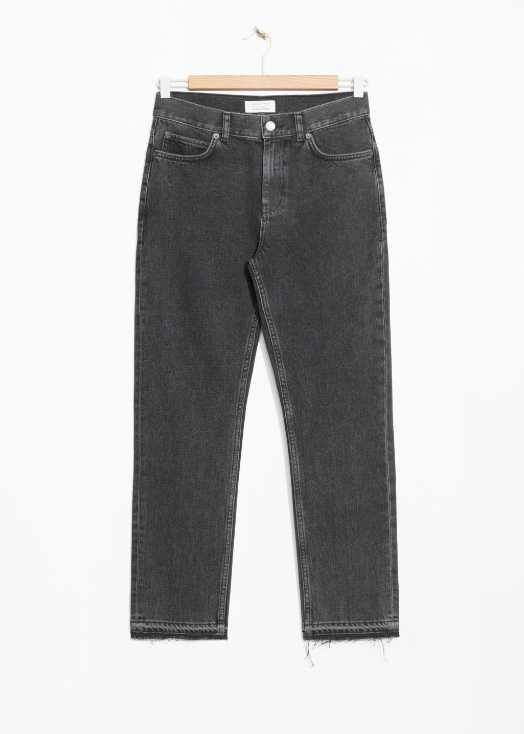 Front image of Stories raw edge slim jeans in black