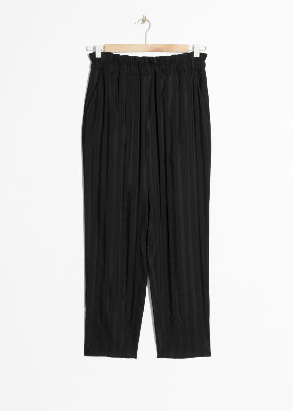 Front image of Stories tapered paperwaist trousers in black