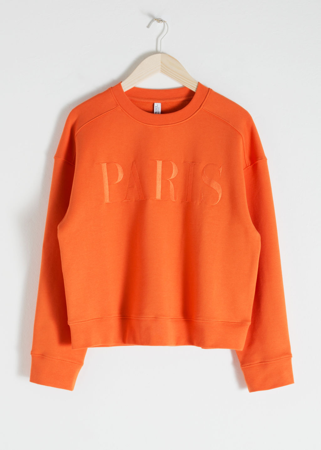 Front image of Stories embroidered pullover in orange