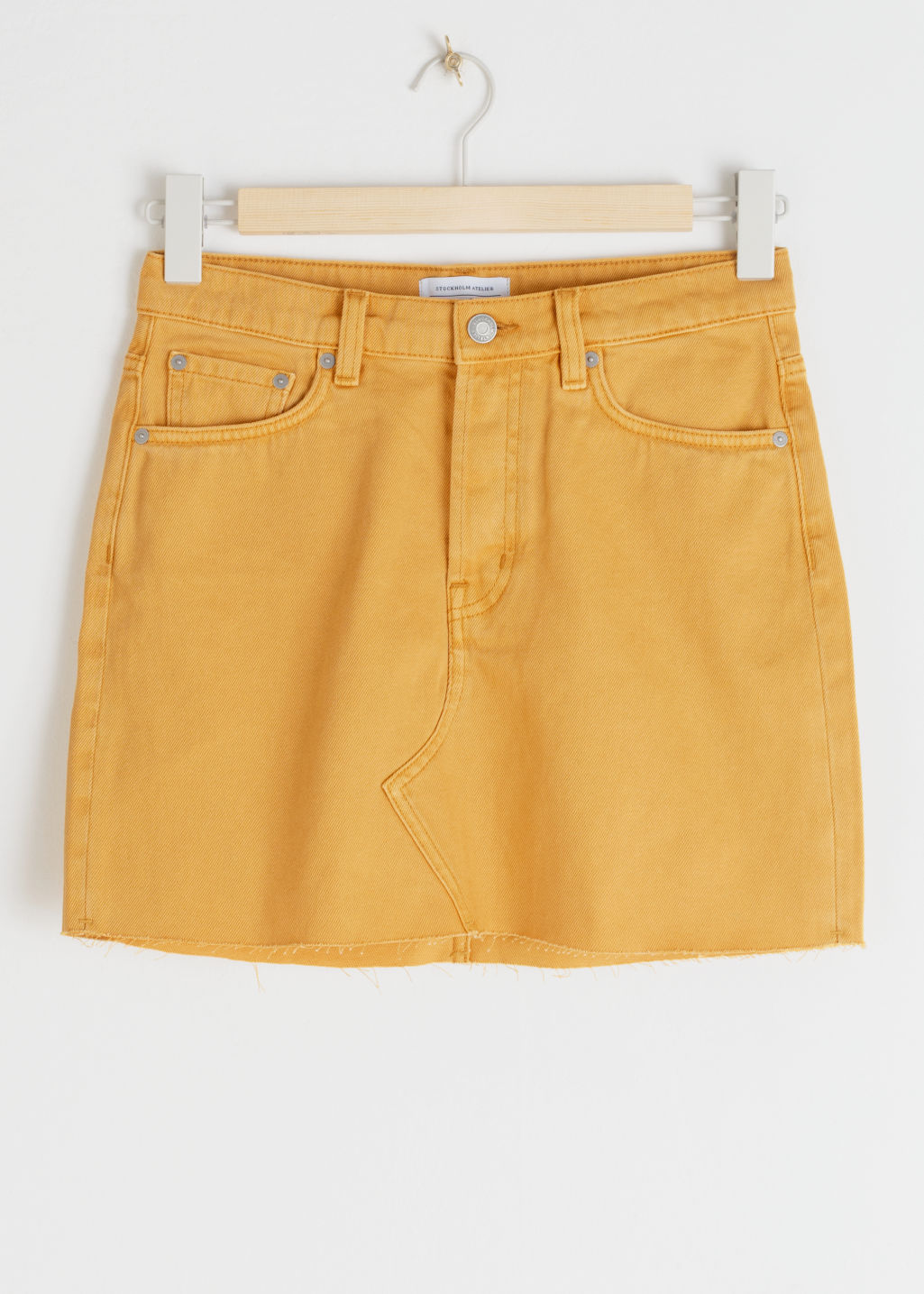 Front image of Stories raw edge denim mini skirt in yellow