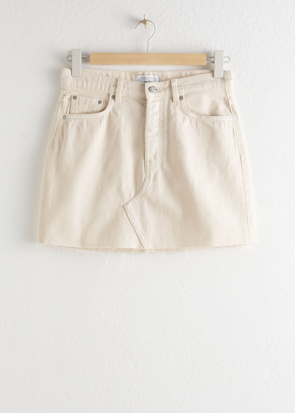 Front image of Stories raw edge denim mini skirt in white