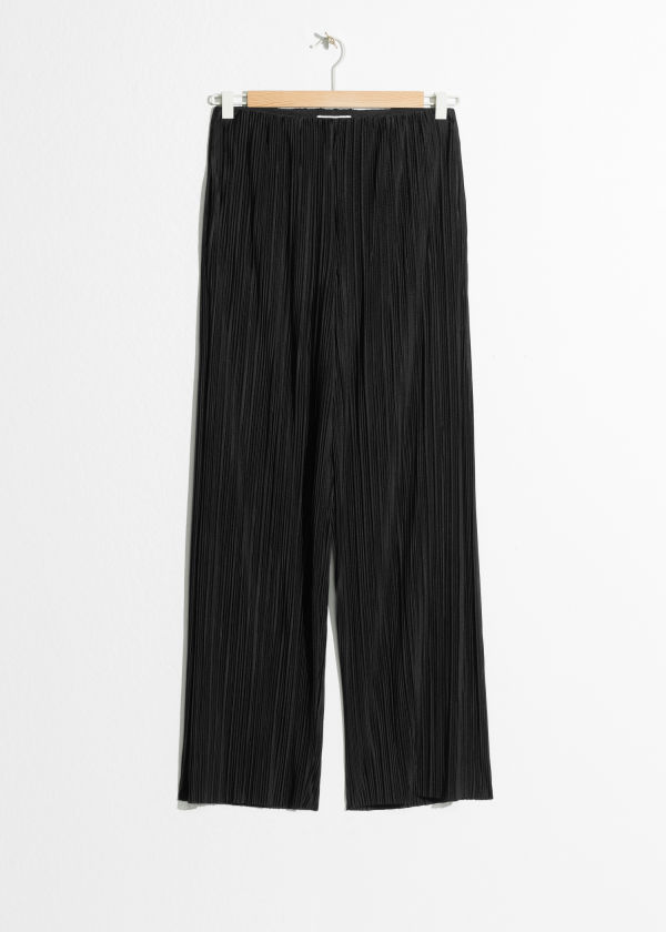 Front image of Stories raw edge pleated trousers in black