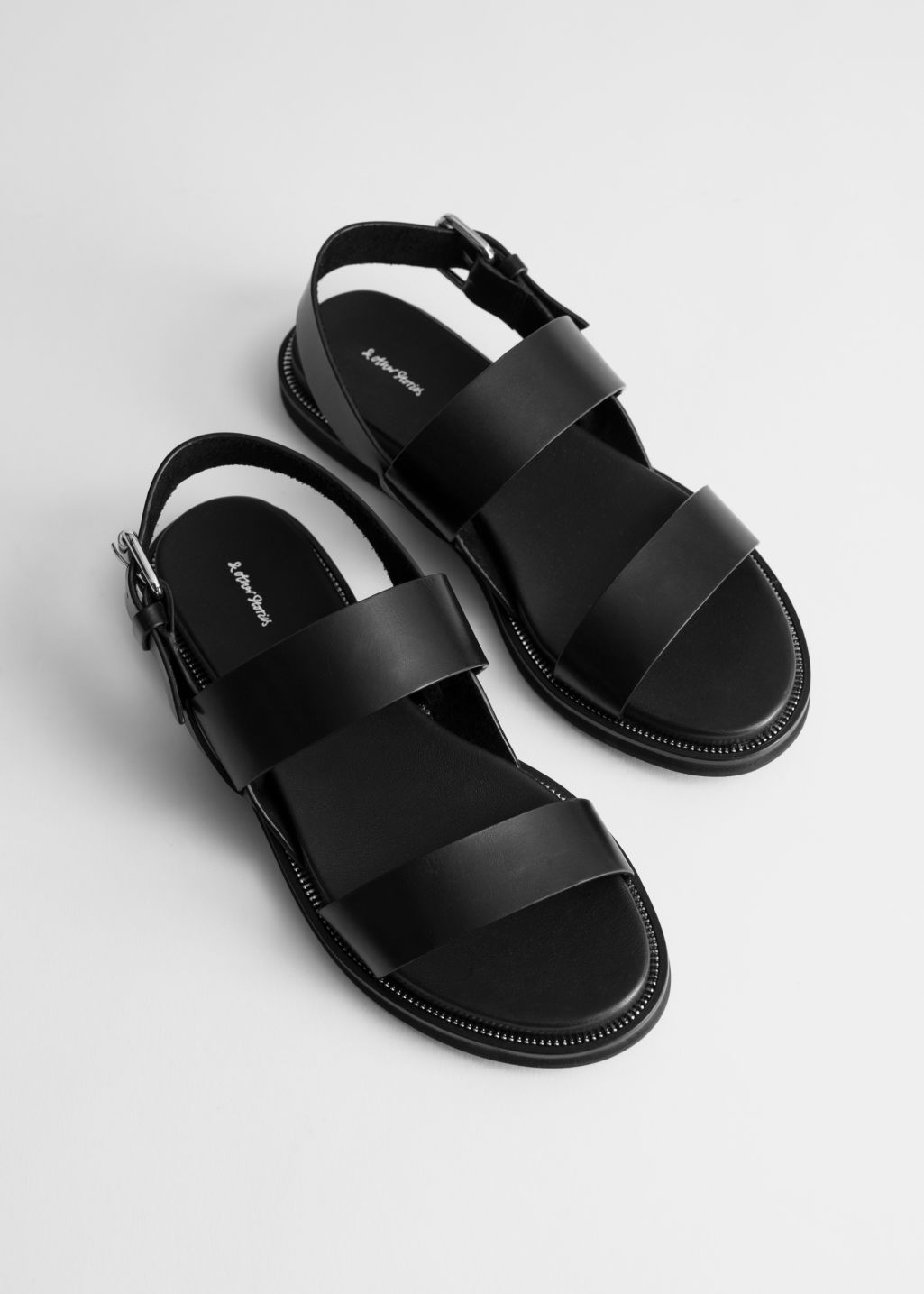 Back image of Stories diagonal strap leather sandals in black