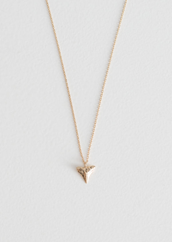 Front image of Stories shark tooth pendant necklace in gold
