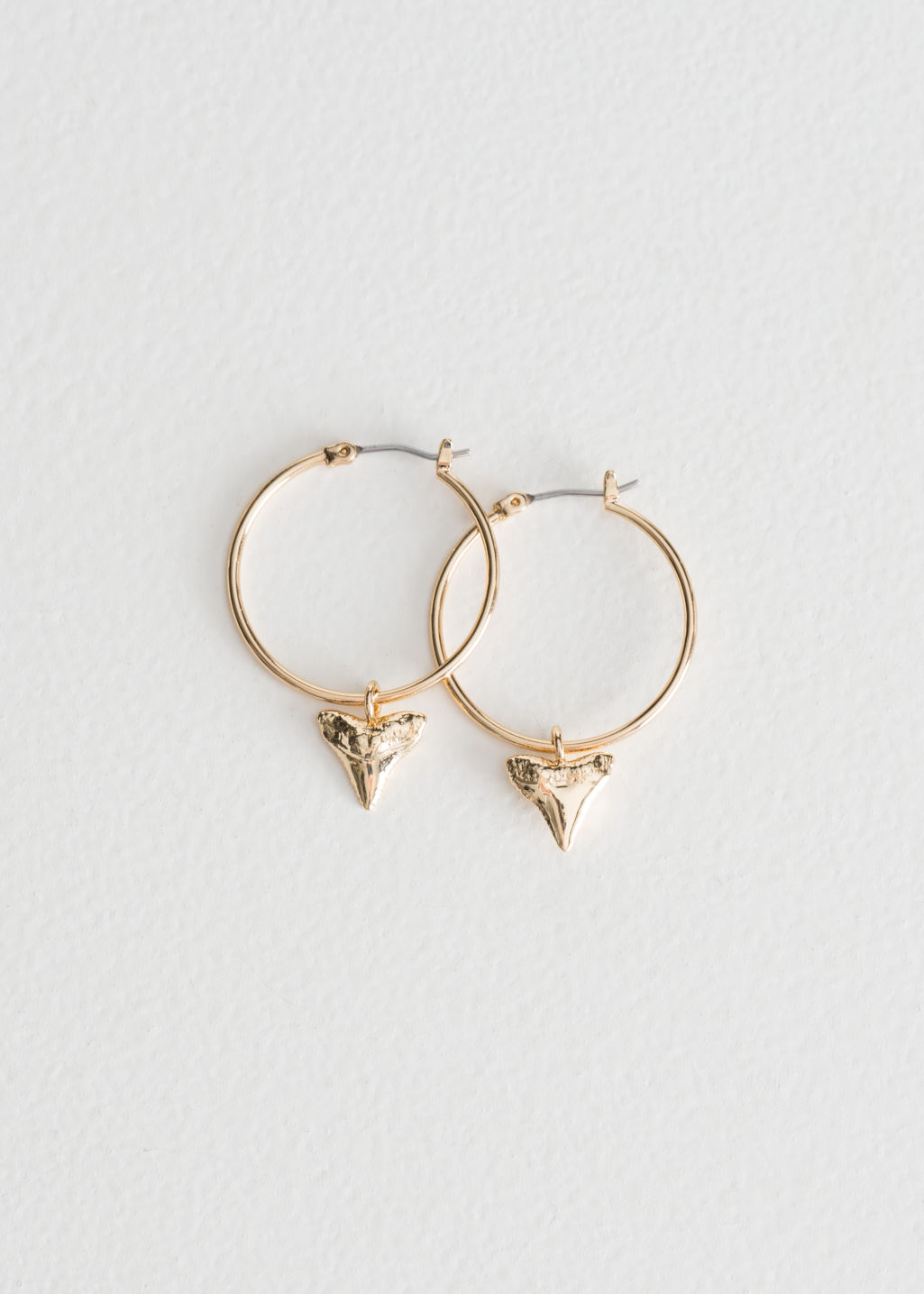 Front image of Stories shark tooth hoop earrings in gold