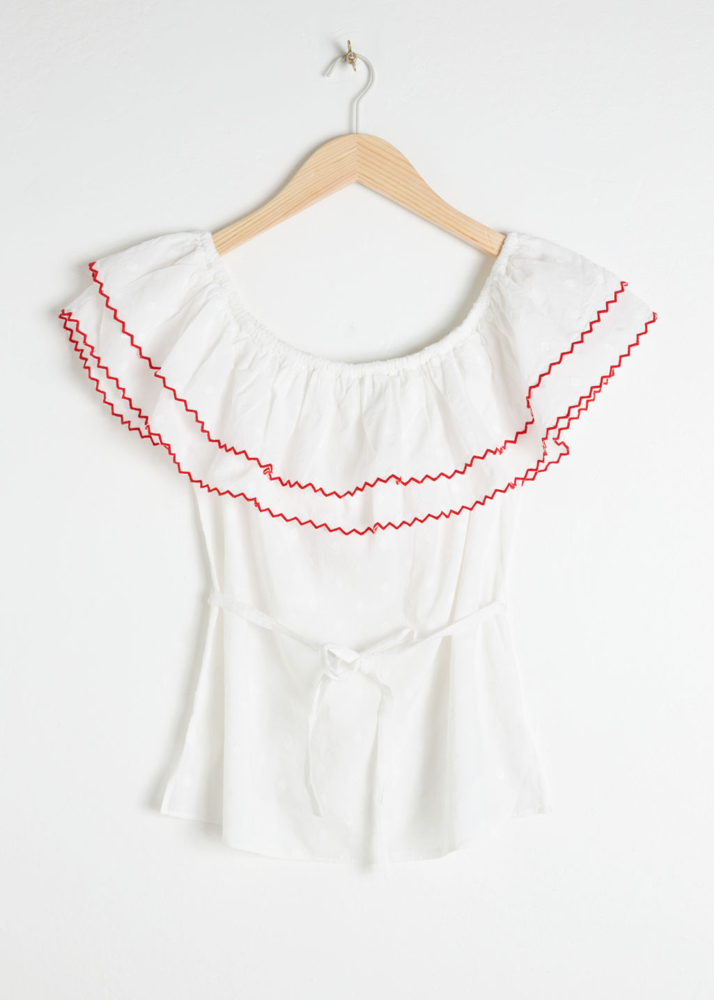Front image of Stories ruffled off shoulder top in white