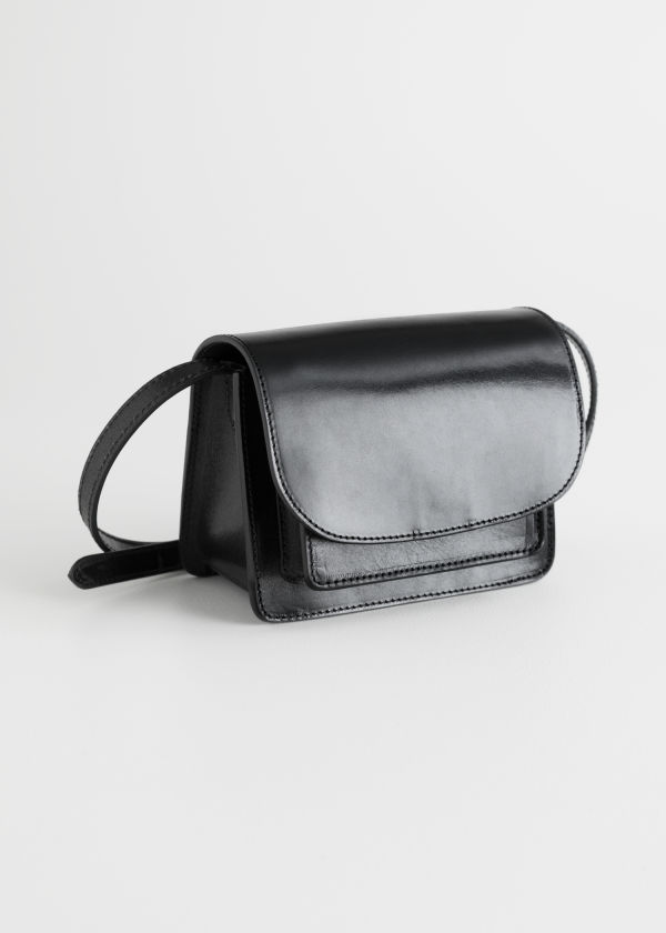 Front image of Stories leather flap over crossbody bag in black
