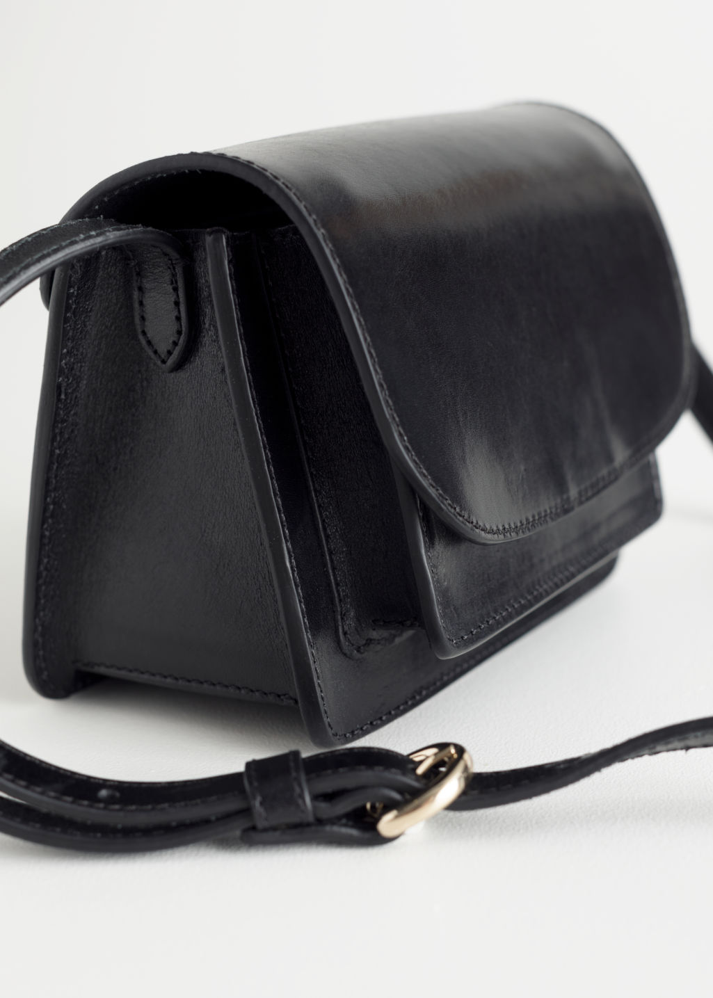 Back image of Stories leather flap over crossbody bag in black